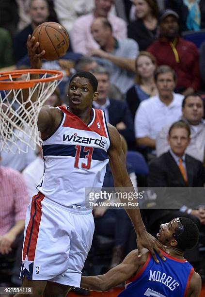 Washington Wizards center Kevin Seraphin goes up over Philadelphia 76ers point guard Darius Morris for a basket during the home opener between the...