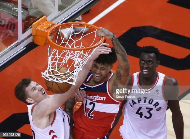 TORONTO ON APRIL 25 Washington Wizards forward Kelly Oubre Jr dunks on Toronto Raptors center Jakob Poeltl as Pascal Siakam looks on as the Toronto...