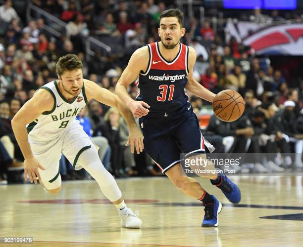 Washington Wizards forward Tomas Satoransky drives against Milwaukee Bucks guard Matthew Dellavedova at Capital One Arena.