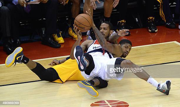 Washington Wizards forward Trevor Ariza passes the ball after going to the floor with Indiana Pacers forward Paul George during the second half of...