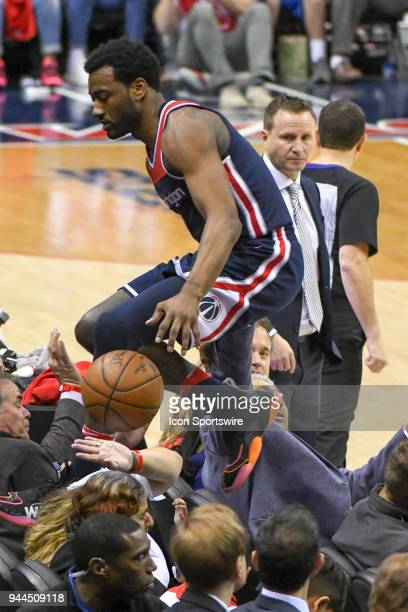 Washington Wizards guard John Wall leaps over the seats going after a loose ball on April 10 2018 at the Capital One Arena in Washington DC The...