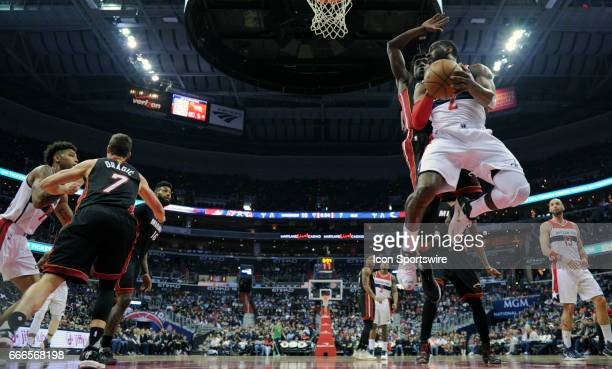 Washington Wizards guard John Wall makes a first half pass under the basket in action against Miami Heat guard Josh Richardson on April 8 at the...