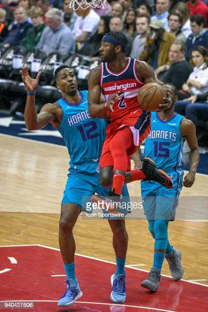 Washington Wizards guard John Wall makes a pass under the basket against Charlotte Hornets center Dwight Howard on March 31 2018 at the Capital One...