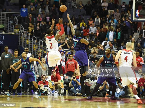 Washington Wizards guard John Wall nails a shot over Charlotte Hornets guard Mo Williams to seal their double overtime win on March 27 2015 in...