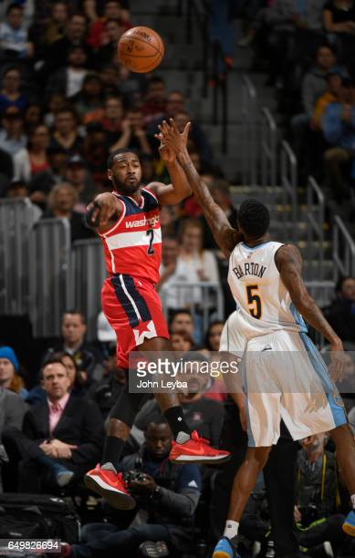 Washington Wizards guard John Wall passes off the ball past Denver Nuggets guard Will Barton during the first quarter on March 8 2017 in Denver...