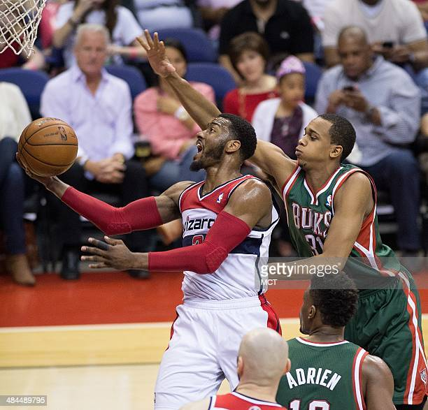 Washington Wizards guard John Wall scores against Milwaukee Bucks center John Henson during the second half of their game played at the Verizon...