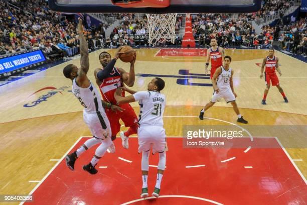 Washington Wizards guard John Wall scores against Milwaukee Bucks guard Eric Bledsoe and forward John Henson on January 15, 2018 at the Capital One...