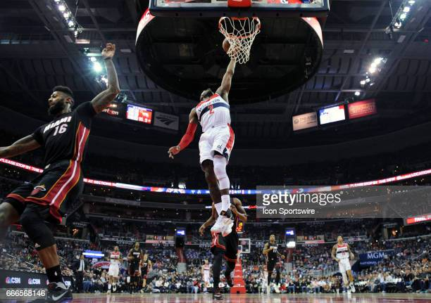Washington Wizards guard John Wall scores in the first half against Miami Heat forward James Johnson on April 8 at the Verizon Center in Washington...