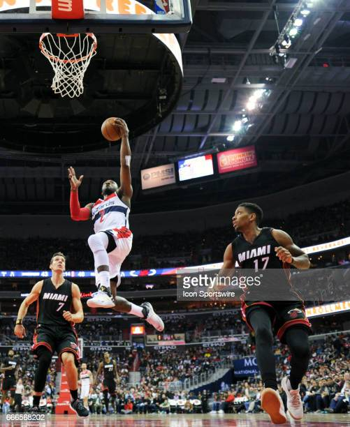 Washington Wizards guard John Wall scores in the first half against Miami Heat guard Rodney McGruder on April 8 at the Verizon Center in Washington...