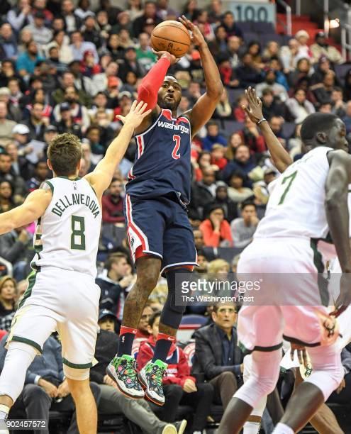 Washington Wizards guard John Wall shoots a step back three pointer over Milwaukee Bucks guard Matthew Dellavedova at Capital One Arena.