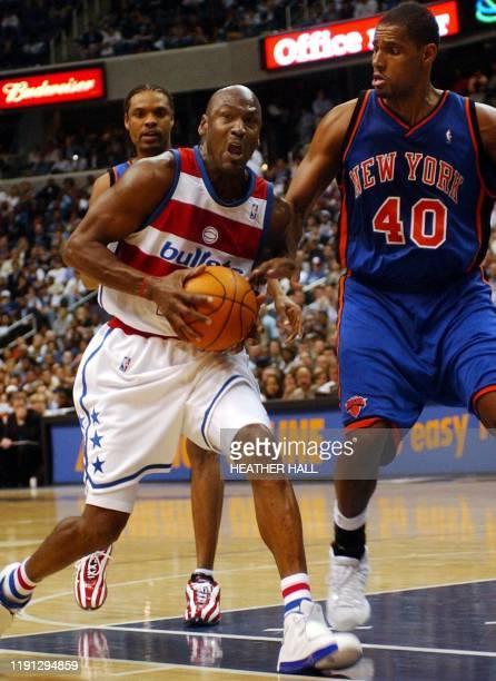 Washington Wizards guard Michael Jordan drives around New York Knicks forward Kurt Thomas in the fourth quarter 14 April 2003 at the MCI Center in...