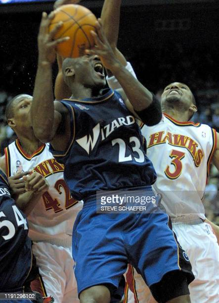 Washington Wizards guard Michael Jordan takes a shot while being guarded by Atlanta Hawks Theo Ratliff and Shareef AbdurRahim during their game at...