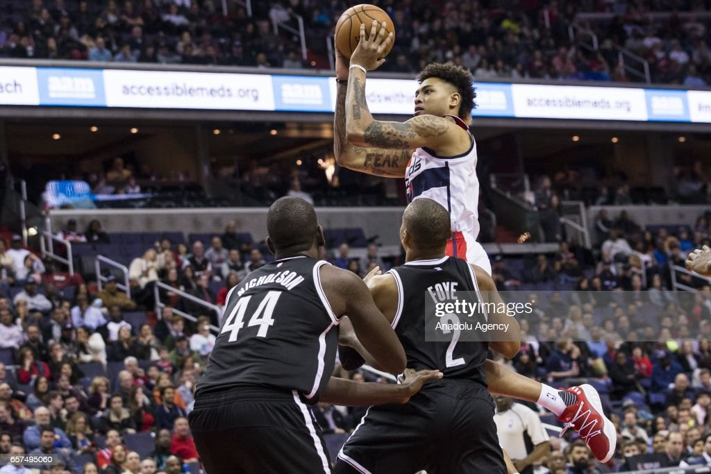 Washington Wizards' Kelly Oubre Jr. (12) soars over Brooklyn Nets Andrew Nicholson (44) and Randy Foye (2) at the Verizon Center in Washington, USA on March 24, 2017. The Wizards topped the Nets 129-109