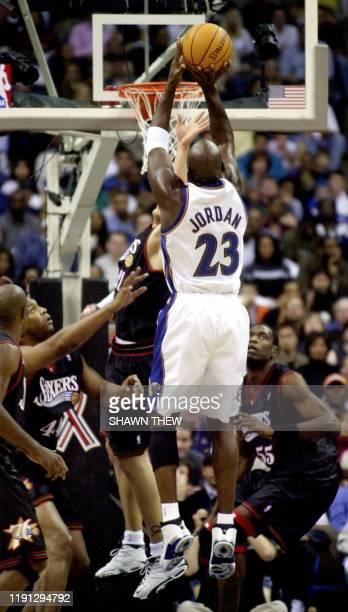 Washington Wizards' Michael Jordan scores two against the Philidelphia 76ers' defense 03 November 2001 at MCI Arena in Washington DC Jordan struggled...