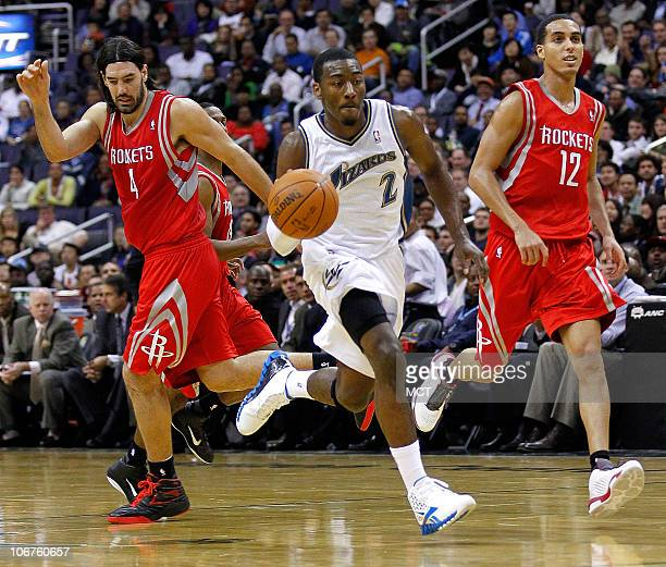 Washington Wizards point guard John Wall drives between Houston Rockets power forward Luis Scola left and shooting guard Kevin Martin during their...
