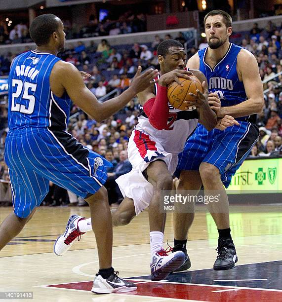Washington Wizards point guard John Wall drives to the basket between Orlando Magic point guard Chris Duhon and power forward Ryan Anderson during...