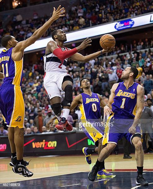 Washington Wizards point guard John Wall drives to the basket for two points between Los Angeles Lakers shooting guard Wesley Johnson and point guard...