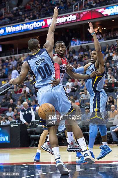 Washington Wizards point guard John Wall passes the ball around the back of Memphis Grizzlies power forward Darrell Arthur and in front of point...