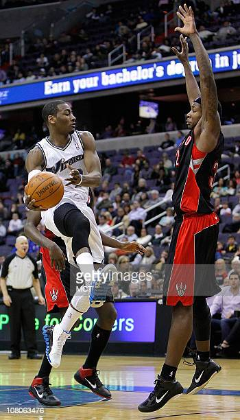 Washington Wizards point guard John Wall passes the ball while being defended by Toronto Raptors power forward Ed Davis during their game played at...