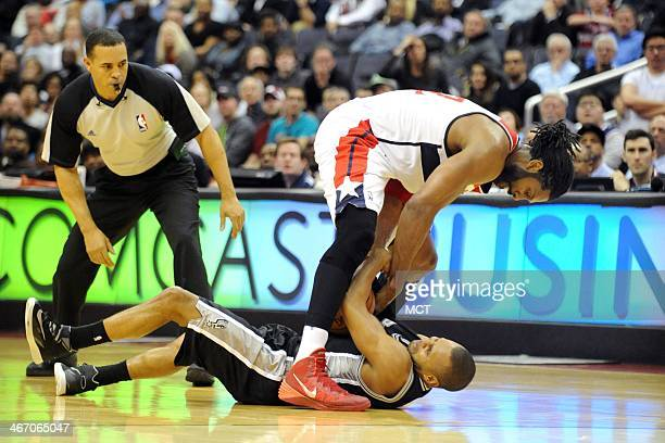 Washington Wizards power forward Nene Hilario and San Antonio Spurs point guard Patty Mills fight for a loose ball during the second overtime at the...