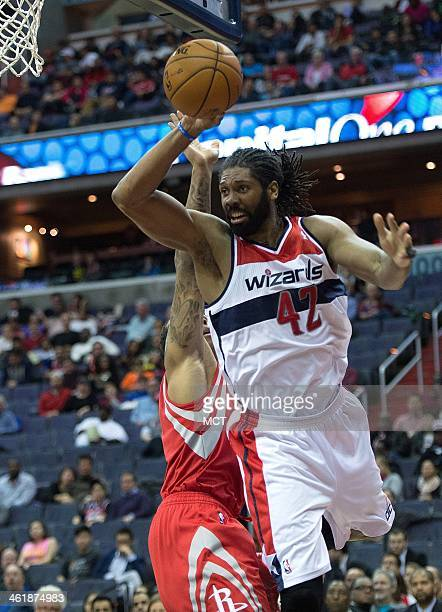 Washington Wizards power forward Nene Hilario passes the ball while being guarded by Houston Rockets shooting guard Francisco Garcia during the...