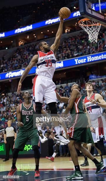 Washington Wizards power forward Trevor Booker slam dunks over Milwaukee Bucks power forward John Henson during the second half of their game played...