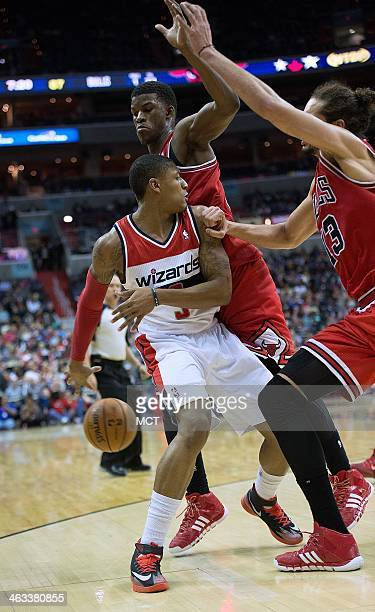 Washington Wizards shooting guard Bradley Beal passes the ball behind his back under pressure from Chicago Bulls shooting guard Jimmy Butler rear and...