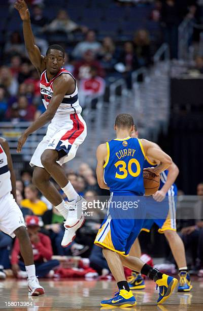 Washington Wizards shooting guard Jordan Crawford right elevates while guarding Golden State Warriors point guard Stephen Curry in the third quarter...