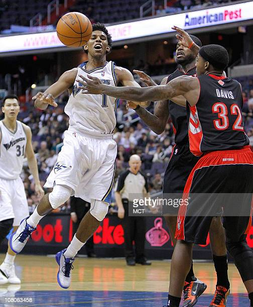 Washington Wizards shooting guard Nick Young looses control of the ball while being defended by Toronto Raptors power forward Ed Davis during their...