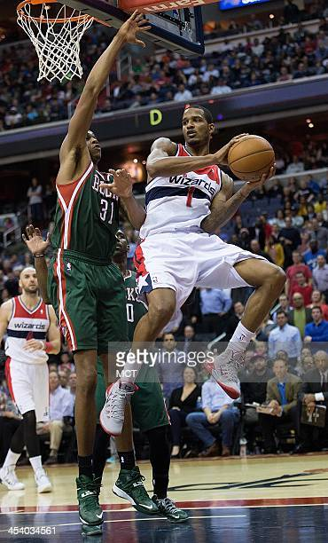 Washington Wizards small forward Trevor Ariza passes the ball while being guarded by Milwaukee Bucks power forward John Henson during the second half...