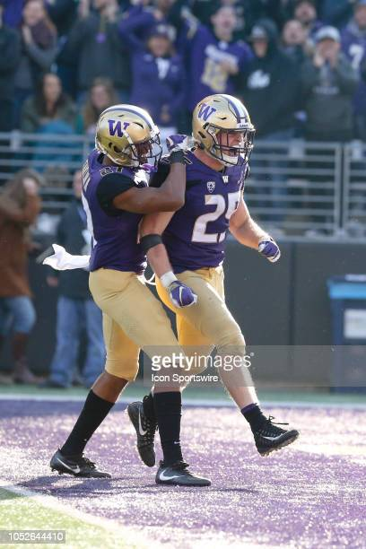 Washington's Ben BurrKirven celebrates with Keith Taylor after making an interception during the college football game between the Washington Huskies...