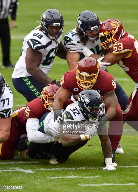 Washingtons Casey Toohill and Jonathan Allen tackle Seahawks running back Chris Carson while Seahawks guard Damien Lewis and tight end Colby...