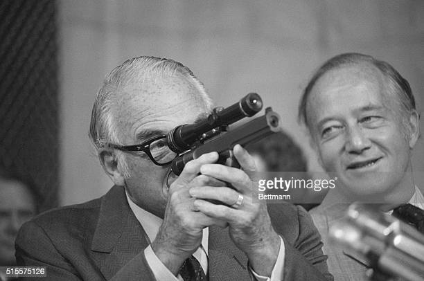 SenBarry Goldwater RAriz sights through a telescope on a dart gun displayed by CIA Director William Colby to the Senate Select Committee on...