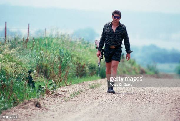 Washinton Redskins' John Riggins walks down a road with a hunting rifle