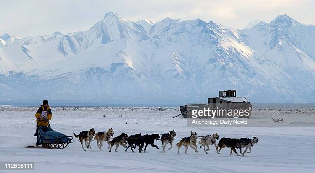 Wasilla musher Heather Hardy is silhouetted against Matanuska Peak and the Chugach Mountains as she runs her team toward the Knik Lake checkpoint...