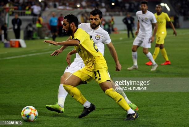 Wasl's midfielder Ahmed AlFaresi is marked by Zawraa's defender Hussein Jwayed during the AFC champions league Group A football match between Iraq's...