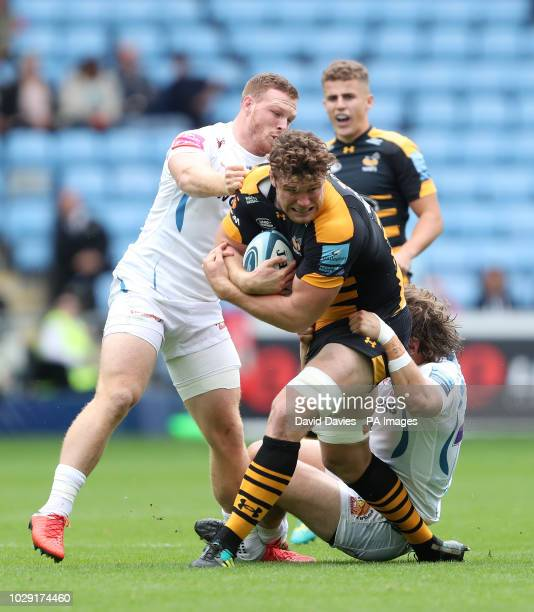 Wasps' Will Rowlands is tackled by Exeter Chief's Alex Hepburn and Sam Simmonds during the Gallagher Premiership match at The Ricoh Arena Coventry
