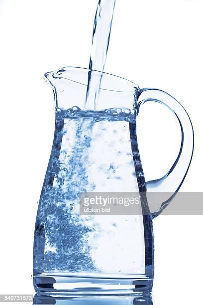 Wasser in eine Karaffe gießen Symbolfoto für Trinkwasser Erfrischung Bedarf und Verbrauch