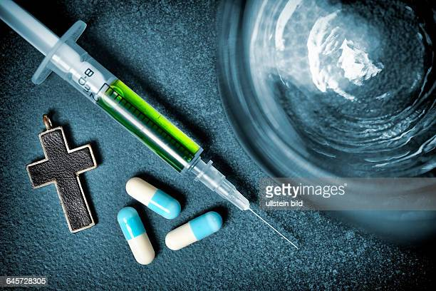 Wasserglas Kreuz Tabletten und Spritze Symbolfoto Sterbehilfe