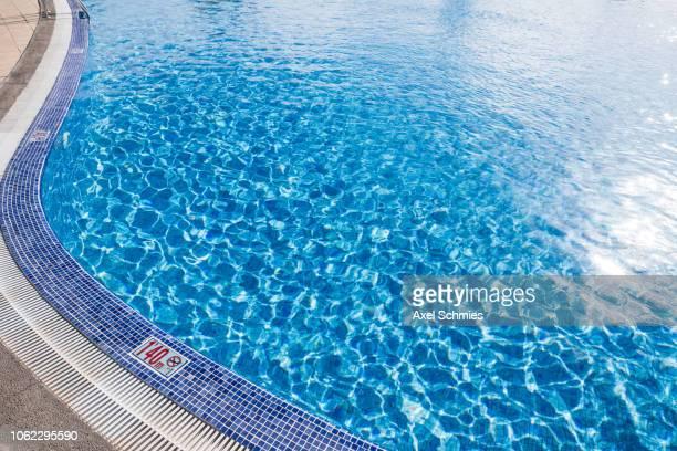 Wasseroberfläche eines Swimming Pools in der Sonne mit Reflektionen
