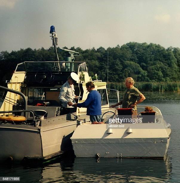 Wasserschutzpolizei auf dem Zeuthener See bei Berlin kontrolliert den Fahrer eines Bootes 1983
