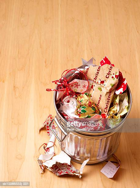 waste bin full of christmas wrapping paper on wooden floor,  high angle view - 宴の後 ストックフォトと画像