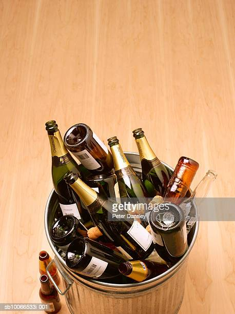 Waste bin full of empty champagne bottles on wooden floor,  high angle view