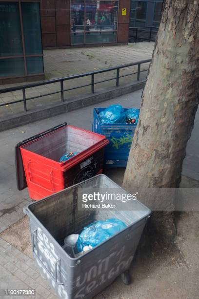 Waste bins beneath an urban tree at Elephant Castle in the south London borough of Southwark on 5th August 2019 in London England