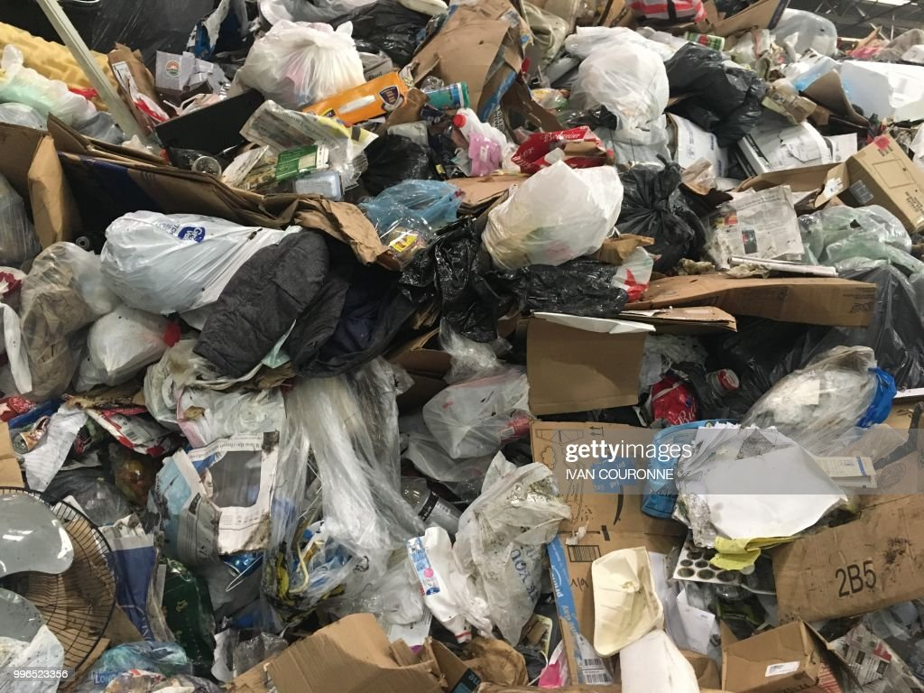 Waste lies in a pile at the District of Columbias Fort Totten Transfer Station in Washington, DC, on July 10, 2018 - Since China, the top global importer of recycable materials for years, has stopped to accept recycables from countries including the United States in January on grounds of 'contamination', the US is struggling with an excess amount of recycable material and no streamlined process to deal with it. As a result, some plastics and paper end up in landfills and some smaller American cities have ended recycling collection programs all together. (Photo by Ivan Couronne / AFP) / TO GO WITH AFP Story by Ivan