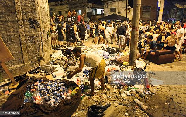 A waste picker collects recyclables in front of a street party thrown one block away from Rio's main red light district Vila Mimosa on January 5 2014...