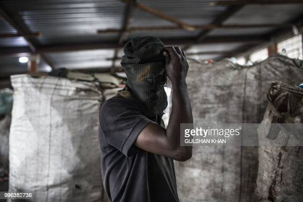 A waste picker wears a balaclava at Mudimu Recycling a buy back centre in Selby Johannesburg where reclaimers bring waste to be weighed and sold on...