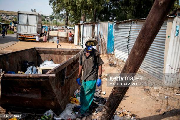 Waste picker wears a dust mask amid concerns over the spread of COVID-19 coronavirus in the densely populated Diepsloot township in Johannesburg, on...