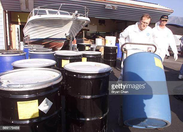 Waste specialists take away containers full of toxic substances from a suspected meth lab at the Santa Paula Airport Saturday A combined law...
