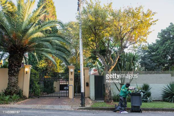 A wastepicker sorts through a bag of garbage from bins placed outside a gated residence in a wealthy suburb of Johannesburg South Africa on Friday...
